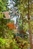 Menino adolescente em um curso das cordas em um parque da aventura da copa de árvore que passa o obstáculo da corda de suspensão imagem de stock