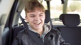 Menino adolescente no banco traseiro no carro vídeos de arquivo