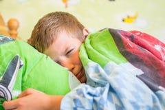 Menino adolescente que dorme na cama fotografia de stock