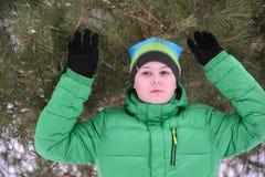 Menino adolescente que está com mãos acima sobre o inverno do pinho foto de stock
