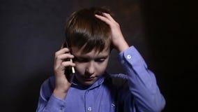 Menino adolescente que fala no estúdio da emoção do telefone video estoque