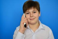 Menino adolescente que fala pela radiotelefonia em um fundo azul fotos de stock royalty free