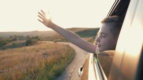 Menino adolescente que olha para fora a janela de carro e que acena sua mão filme