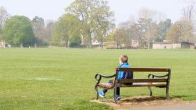 Menino adolescente que senta-se no banco no parque britânico vazio vestido no kit de treinamento imagens de stock