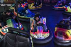 Menino adolescente que tem o divertimento para conduzir um carro abundante na feira de divertimento, imagem de borrão do moviment Imagem de Stock