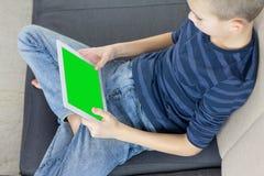 Menino adolescente que usa o PC da tabuleta com tela verde ao sentar-se no sofá em casa Feche acima do polegar que enrola acima a fotos de stock