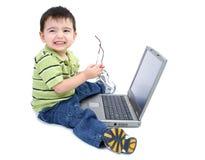 Menino adorável com funcionamento de vidros no portátil sobre o branco Foto de Stock Royalty Free