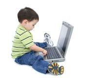 Menino adorável com trabalho no portátil sobre o branco Foto de Stock