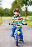 Menino adorável da criança no capacete vermelho e na capa de chuva colorida que montam o seu Imagens de Stock Royalty Free