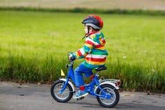 Menino adorável da criança no capacete vermelho e na capa de chuva colorida que montam o seu Foto de Stock