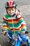 Menino adorável da criança no capacete vermelho e na capa de chuva colorida que montam o seu Fotografia de Stock Royalty Free