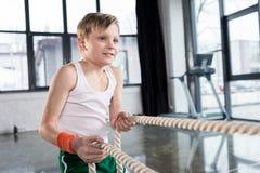 Menino adorável da criança no treinamento do sportswear com cordas no estúdio da aptidão imagens de stock