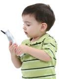 Menino adorável da criança que fala em um telefone sem corda sobre o branco imagens de stock royalty free