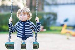 Menino adorável da criança que tem o balanço da corrente do divertimento no playgroun exterior Imagens de Stock