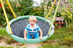 Menino adorável da criança que tem o balanço da corrente do divertimento no playgroun exterior Imagem de Stock