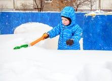 Menino adorável dos anos de idade da árvore que trabalha com pá a neve foto de stock