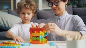 Menino adorável e sua mãe que jogam com blocos da construção no apartamento