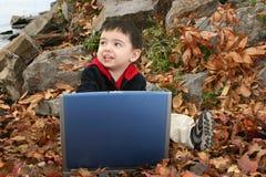 Menino adorável nas folhas com portátil Imagem de Stock Royalty Free