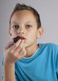 Menino adorável que come bolinhos Imagem de Stock Royalty Free