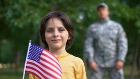 Menino adorável que guarda a bandeira americana, soldado masculino que está atrás, futuro seguro filme