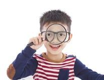 Menino adorável que guarda uma lente de aumento e que olha completamente Imagens de Stock Royalty Free