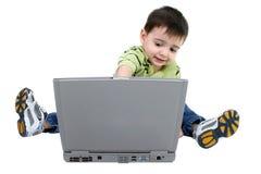 Menino adorável que trabalha no portátil sobre o branco Foto de Stock