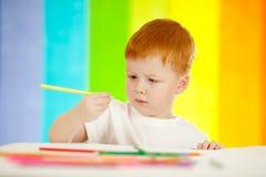 Menino adorável Red-haired no fundo do arco-íris Imagem de Stock