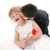 Menino adorável da criança que dá a menina dos anos de idade consideravelmente quatro um beijo Fotografia de Stock