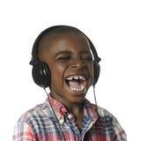 Menino africano com fones de ouvido que escuta a música fotografia de stock