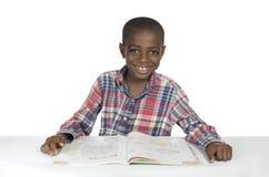 Menino africano com livro de texto foto de stock