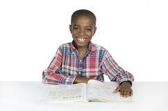 Menino africano com livro de texto Fotos de Stock Royalty Free
