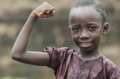 Menino africano forte considerável que mostra os músculos no fundo isolado borrado fotos de stock