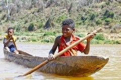 Menino africano malgaxe novo que enfileira a canoa tradicional Imagem de Stock