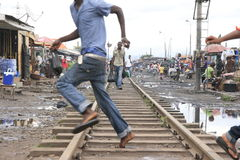 Menino africano novo que anda uma estrada de ferro velha em Accra Imagem de Stock Royalty Free