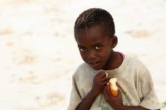 Menino africano pequeno com parte de pão imagens de stock
