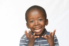 Menino africano pequeno surpreendido entusiasmado sobre a obtenção de um presente isolado no branco imagens de stock