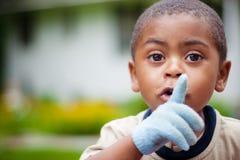Menino afro-americano bonito com o dedo nos bordos Fotos de Stock