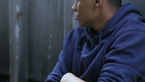 Menino afro-americano ofendido que senta-se no assoalho, problemas na sociedade, racismo vídeos de arquivo