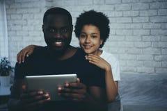 Menino afro-americano que abraça o pai que interage foto de stock royalty free