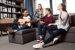 Menino afro-americano que joga a guitarra acustic quando seus amigos que escutam e que cantam em casa imagens de stock royalty free