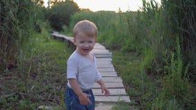 Menino agradável bonito da criança que anda na ponte de madeira com os pés descalços no ar livre entre juncos altos filme