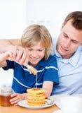 Menino alegre e seu pai que põr o mel sobre waffles Fotografia de Stock Royalty Free