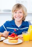 Menino alegre que come waffles com morangos Foto de Stock
