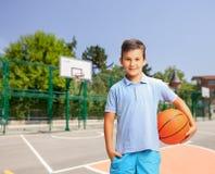 Menino alegre que guarda um basquetebol em uma corte exterior Fotos de Stock Royalty Free