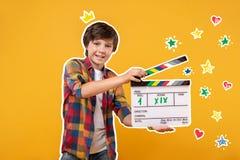 Menino alegre que guarda um clapstick e gravar um filme foto de stock royalty free