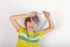 Menino alegre que guarda um limo do brilho na frente dele imagem de stock