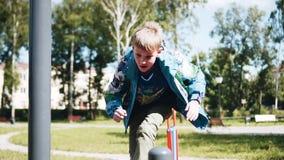 Menino alegre que joga no campo de jogos Corridas acima e saltos para a frente Tiros agrad?veis Playback lento video estoque