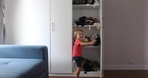 Menino alegre que joga no vestuário em casa