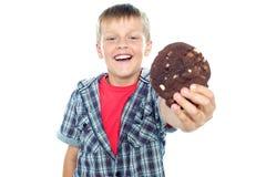 Menino alegre que oferece lhe um bolinho do chocolate Imagem de Stock