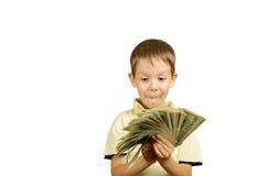 Menino alegre que olha uma pilha de 100 contas dos dólares americanos Fotografia de Stock Royalty Free